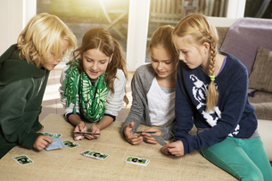 Four children playing card game in living roomの写真素材 [FYI04341316]