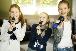 Three girls singing with microphoneの写真素材 [FYI04341317]