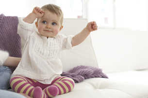 Smiling baby girl with outstrechted arms sitting on sofaの写真素材 [FYI04341321]