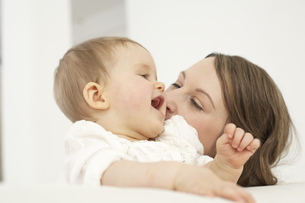 Mother kissing her smiling baby girlの写真素材 [FYI04341323]