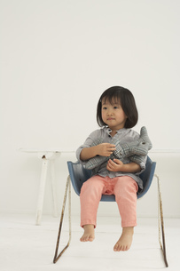 Little Asian girl with soft toy sitting on a chairの写真素材 [FYI04341337]