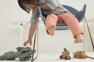 Little Asian girl sitting on a chair gribbing her soft toyの写真素材 [FYI04341341]