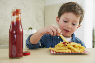 Germany, Munich, Boy eating French fries with ketchupの写真素材 [FYI04341425]