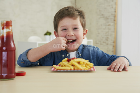 Germany, Munich, Boy eating French fries with ketchupの写真素材 [FYI04341426]
