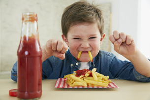 Germany, Munich, Boy eating French fries with ketchupの写真素材 [FYI04341427]