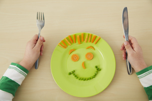Germany, Munich , Boy eating peas and carrots showing anthroの写真素材 [FYI04341428]