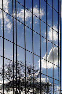 Clouds reflecting in glass front of an office buildingの写真素材 [FYI04341457]