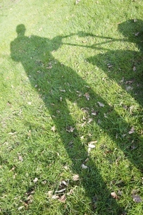 Germany, Petershagen, Shadow of a man mowing lawnの写真素材 [FYI04341484]