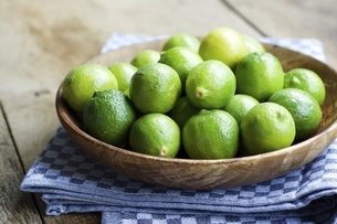 Key limes, Citrus aurantiifolia, in a wooden bowlの写真素材 [FYI04341577]