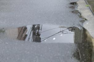 Japan, Tokyo, Shinjuku, power pylon reflecting in puddleの写真素材 [FYI04341601]
