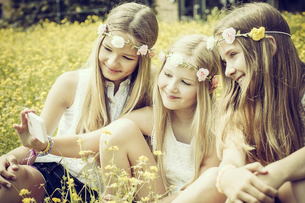 Portrait of three girls wearing floral wreaths taking a selfの写真素材 [FYI04341612]