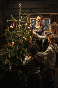Mother and her three children decorating Christmas tree in aの写真素材 [FYI04341614]