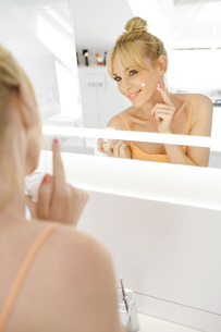 Smiling woman looking at her mirror image while applying facの写真素材 [FYI04341624]