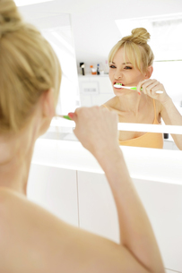 Woman looking at her mirror image while brushing teethの写真素材 [FYI04341627]