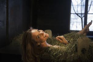 Smiling woman taking hay bath in a tubの写真素材 [FYI04341628]
