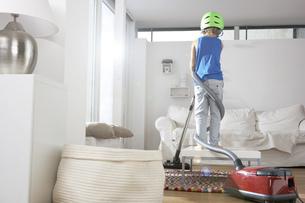 Boy in living room tangled in vacuum cleanerの写真素材 [FYI04341650]