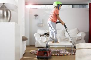 Boy in living room hooveringの写真素材 [FYI04341651]