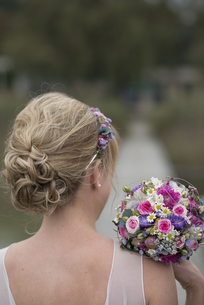 Germany, blond bride with updo and bridal bouquet, back viewの写真素材 [FYI04341672]