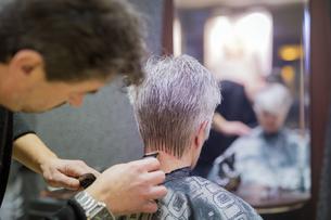 Senior woman getting new hair cut, hairdresser shaving neckの写真素材 [FYI04341710]