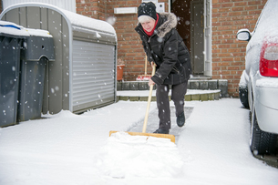 Germany, Grevenbroich, woman shoveling snow in front of housの写真素材 [FYI04341750]