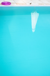 Reflection of a parasol in a swimmingpoolの写真素材 [FYI04341778]