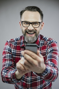 Portrait of excited man looking at smartphoneの写真素材 [FYI04341796]