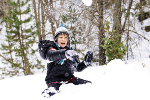 Happy boy playing with snow in the woodsの写真素材 [FYI04341801]