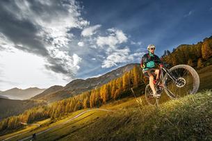 Austria, Altenmarkt-Zauchensee, young mountain biker drivingの写真素材 [FYI04341887]