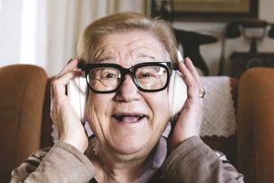 Portrait of happy elderly lady hearing music with headphonesの写真素材 [FYI04341893]