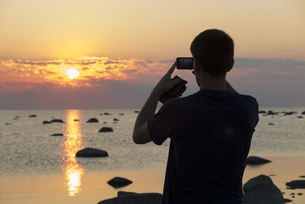 Estonia, Kaesmu, teenager taking a photography of sunset witの写真素材 [FYI04341912]