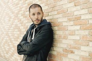 Portrait of man leaning on brick wallの写真素材 [FYI04341927]