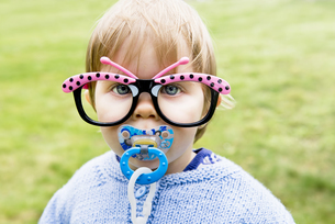Portrait of baby girl with pacifier wearing fun butterfly glの写真素材 [FYI04341943]