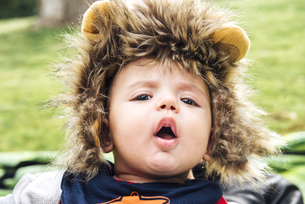 Baby with open mouth wearing a lion hatの写真素材 [FYI04341948]