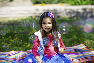 Little girl outdoors surrounded by saop bubblesの写真素材 [FYI04341955]