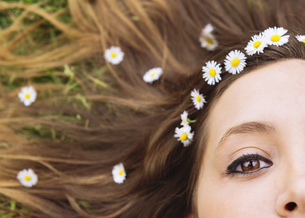Woman lying on a meadow wearing daisies in her hair, close-uの写真素材 [FYI04341957]