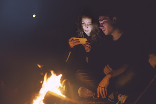 Young couple sitting together at the campfire looking at celの写真素材 [FYI04341983]
