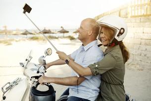 Spain, Majorca, Alcudia, couple with selfie stick on motor sの写真素材 [FYI04341993]