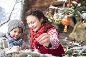 Austria, Altenmarkt-Zauchensee, woman and boy decorating Chrの写真素材 [FYI04342053]