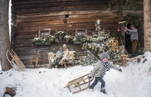 Austria, Altenmarkt-Zauchensee, family in front of farmhouseの写真素材 [FYI04342054]
