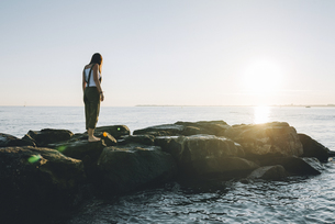 France, Pornichet, woman standing on rocks at seafront by suの写真素材 [FYI04342071]