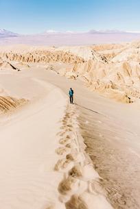 Chile, Atacama Desert, man climbing a duneの写真素材 [FYI04342120]