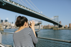 USA, New York City, young woman using coin operated binoculaの写真素材 [FYI04342126]