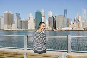 USA, New York City, young woman sitting in front of the skylの写真素材 [FYI04342129]