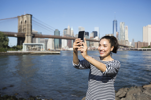 USA, New York City, young woman  taking a selfie with smartpの写真素材 [FYI04342131]