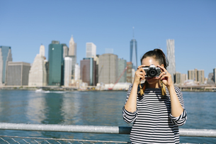 USA, New York City, young woman standing in front of skylineの写真素材 [FYI04342135]