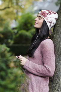 Portrait of young woman leaning against tree trunk hearing mの写真素材 [FYI04342263]