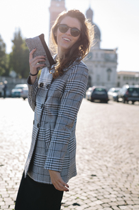 Italy, Vicenza, smiling brunette woman wearing checkered coaの写真素材 [FYI04342271]