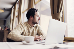 Man with laptop sitting in a coffee shop looking through winの写真素材 [FYI04342347]