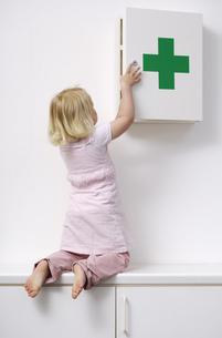 Blond little girl opening medicine cabinetの写真素材 [FYI04342379]