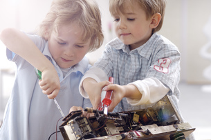 Two little boys disassembling an old radioの写真素材 [FYI04342380]